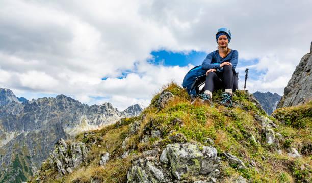 Bir kask genç bir çekici kadın (turist), bir sırt çantası ve trekking direkleri ile zirve üzerinde oturan dinlenir. Arka planda güzel bir sonbahar dağ manzara ve gökyüzünde bulutlar. stok fotoğrafı