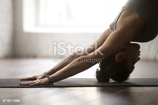 istock Young attractive woman in adho mukha svanasana pose, white studi 674671588