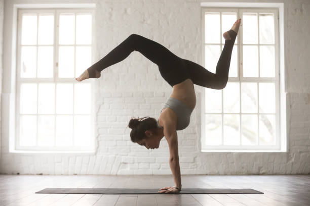 Young attractive woman in Adho Mukha Vrksasana pose, white studi stock photo
