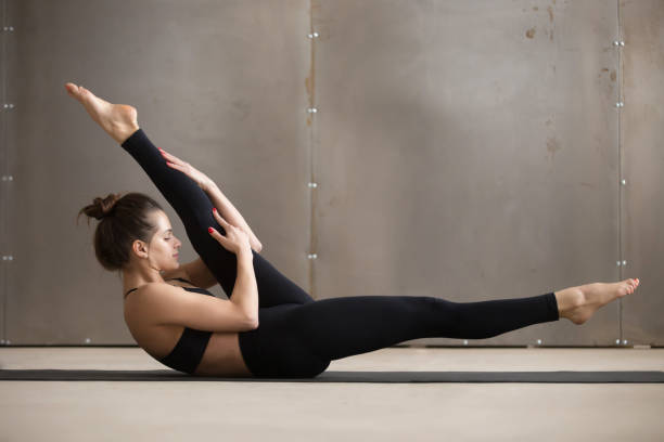 Young attractive woman in alternate leg stretch pose, grey studi Young attractive woman doing alternate leg stretch, fitness exercise, working out, wearing black sportswear, cool urban style, full length, grey studio background, side view hamstring stock pictures, royalty-free photos & images