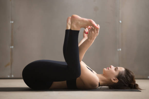 Young attractive woman in Ananda Balasana pose, grey studio back Young attractive woman practicing yoga, stretching in Ananda Balasana exercise, Happy Baby pose, working out, wearing black sportswear, cool urban style, full length, grey studio background, side view apanasana stock pictures, royalty-free photos & images