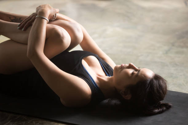 Young attractive woman in Apanasana pose, close up Young attractive sporty woman practicing yoga at home, lying in Knees to Chest exercise, Apanasana pose, working out, wearing sportswear, black shorts and top, indoor close up image, floor background apanasana stock pictures, royalty-free photos & images
