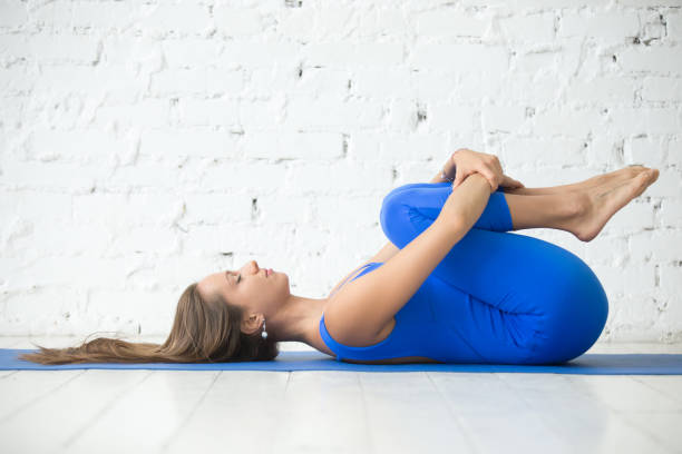 Young attractive woman in Apanasana pose, white studio backgroun Attractive woman practicing yoga, Knees to Chest exercise, Apanasana pose, working out, wearing sportswear, blue suit, indoor full length, white loft studio background. apanasana stock pictures, royalty-free photos & images