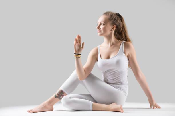 junge attraktive frau in ardha matsyendrasana posiert, graues studio - gymnastik tattoo stock-fotos und bilder