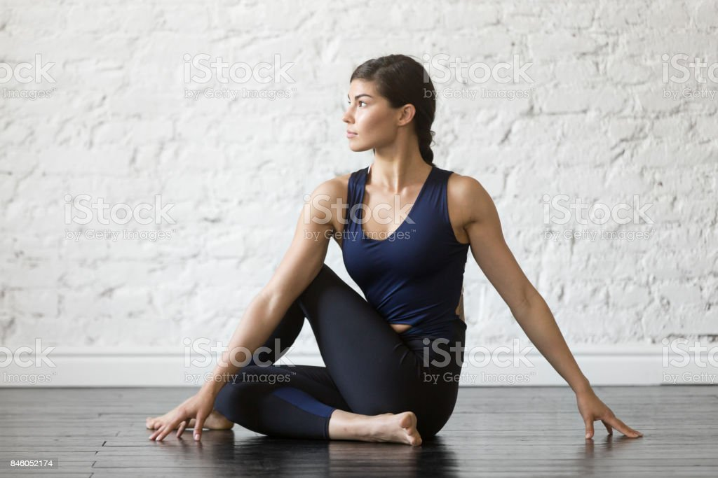 Young attractive woman in Ardha Matsyendrasana pose, studio background stock photo