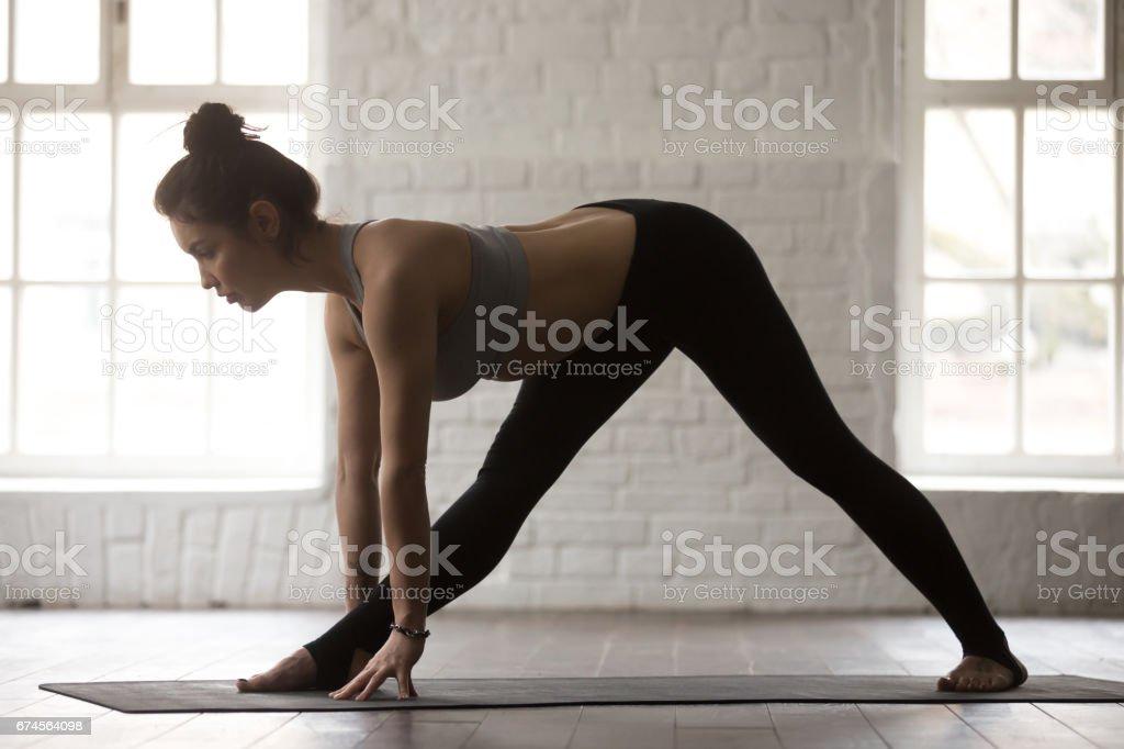 Young attractive woman in Ardha Parsvottanasana pose, white loft stock photo