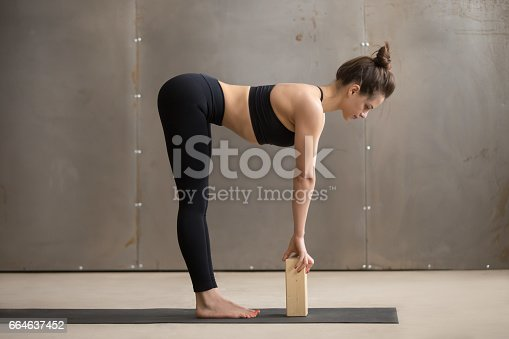 istock Young attractive woman in Ardha uttanasana pose with block, stud 664637452