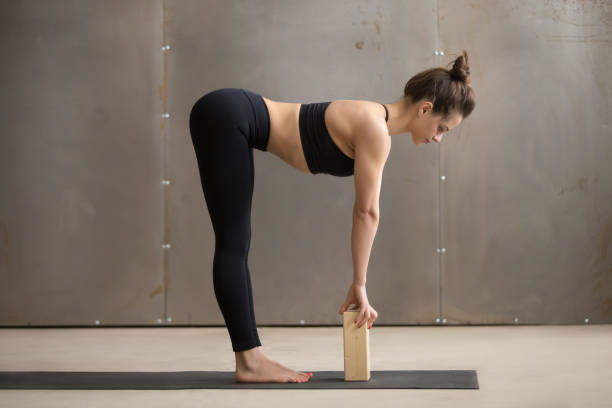 Young attractive woman in Ardha uttanasana pose with block, stud Young attractive yogi woman practicing yoga, standing in head to knees, Ardha uttanasana exercise, using block, Standing Half forward bend pose, working out, cool urban style, full length, grey studio namaskard geothermal area stock pictures, royalty-free photos & images