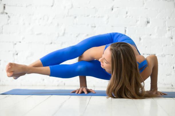 young attractive woman in astavakrasana pose, white studio backg - jumpsuit blau stock-fotos und bilder