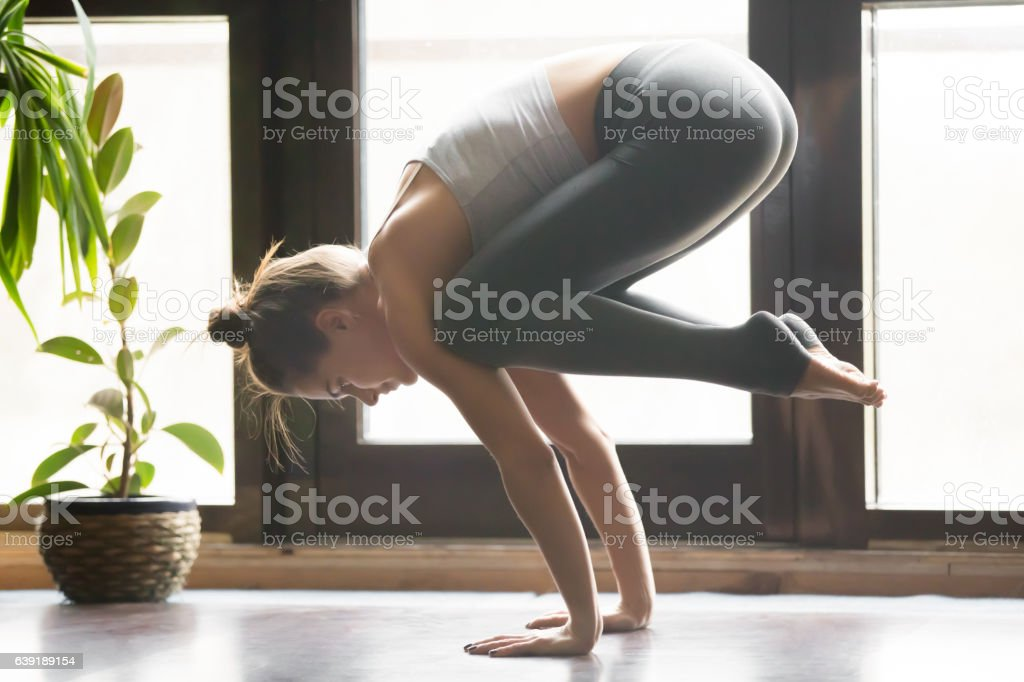 Young attractive woman in Bakasana pose, home interior backgroun Young attractive woman practicing yoga, standing in Crane, Bakasana pose, working out, wearing sportswear, grey pants, bra, indoor full length, home interior background, living room Active Lifestyle Stock Photo
