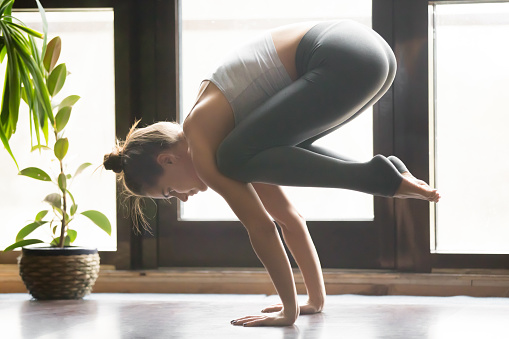 Young Attractive Woman In Bakasana Pose Home Interior Backgroun Stock Photo - Download Image Now