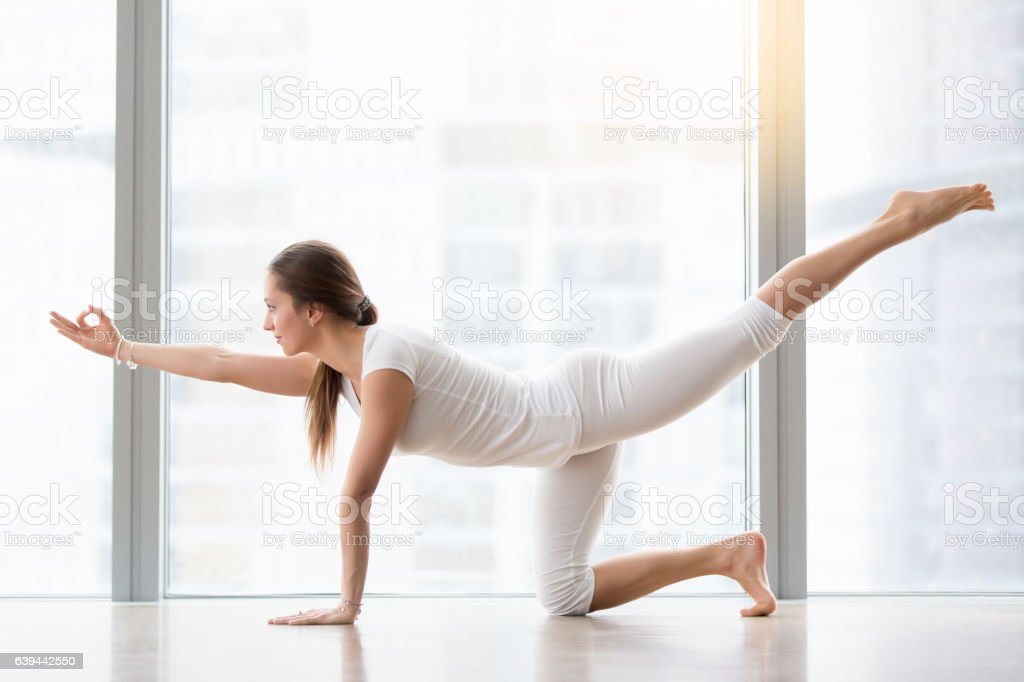 Young attractive woman in Bird dog pose against floor window stock photo