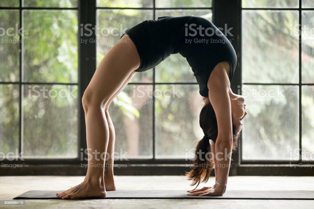 Young attractive woman in Bridge pose, studio background stock photo
