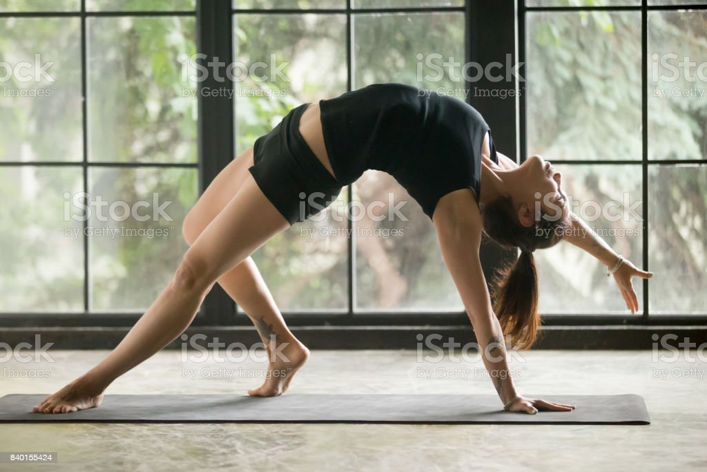 Young attractive woman in Camatkarasana pose, studio background stock photo
