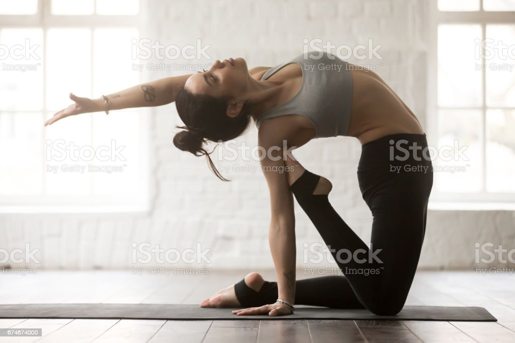 Young attractive woman in Camel pose, white loft studio backgrou stock photo