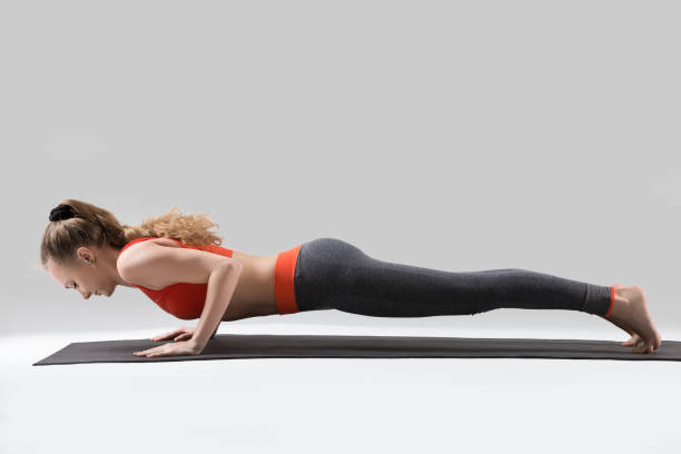 Young attractive woman in chaturanga dandasana pose, grey studio Young attractive woman practicing yoga, standing in four limbed staff exercise, doing Push ups or press ups, chaturanga dandasana pose, working out, wearing red tank top, pants, full length, studio namaskard geothermal area stock pictures, royalty-free photos & images