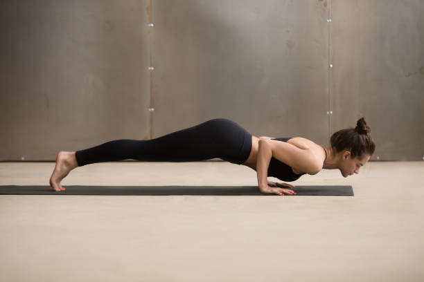 Young attractive woman in chaturanga dandasana pose, grey studio Young woman practicing yoga, standing in four limbed staff exercise, doing Push ups, press ups, chaturanga dandasana pose, working out, wearing black sportswear, cool urban style, full length, studio namaskard geothermal area stock pictures, royalty-free photos & images