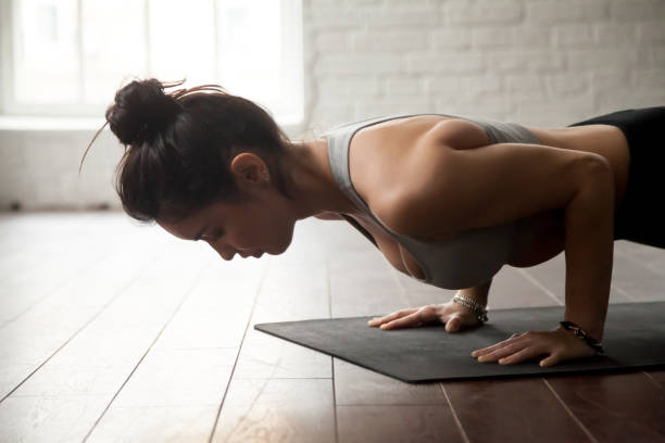 Young attractive woman in chaturanga dandasana pose, loft studio Young attractive woman practicing yoga, standing in chaturanga dandasana exercise, four limbed staff, Push ups or press ups pose, working out, white loft studio background, closeup waist up stock pictures, royalty-free photos & images