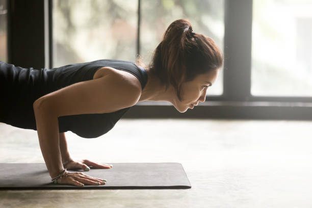 Young attractive woman in chaturanga dandasana pose, studio, side view Young sporty attractive woman practicing yoga, doing Push ups, press ups, four limbed staff exercise, chaturanga dandasana pose, working out wearing black top, indoor close up image, studio background namaskard geothermal area stock pictures, royalty-free photos & images