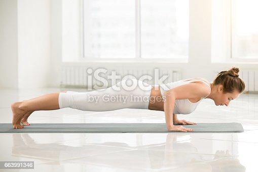 675173150 istock photo Young attractive woman in chaturanga dandasana pose, white color 663991346