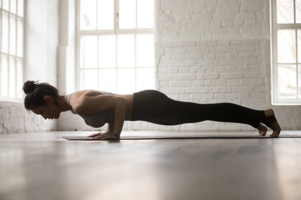Young attractive woman in chaturanga dandasana pose, white loft Young attractive woman practicing yoga, standing in chaturanga dandasana exercise, four limbed staff, Push ups or press ups pose, working out, white loft studio background, full length, side view namaskard geothermal area stock pictures, royalty-free photos & images