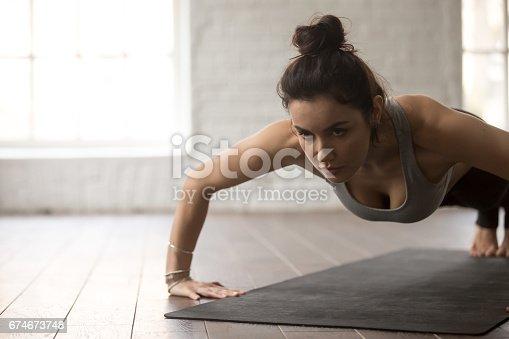 675173150 istock photo Young attractive woman in chaturanga dandasana pose, white loft 674673748