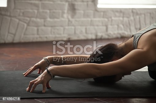 Young attractive yogi woman practicing yoga concept, sitting in Child exercise, Balasana pose, working out, wearing black sportswear, hands close up, white loft studio background