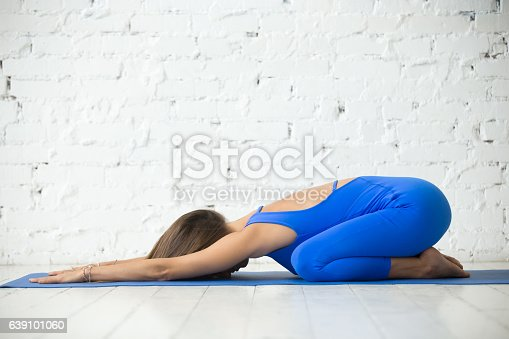 istock Young attractive woman in Child pose, white studio background 639101060