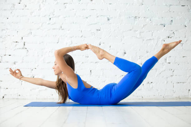 Young attractive woman in Dhanurasana pose, white studio backgro stock photo