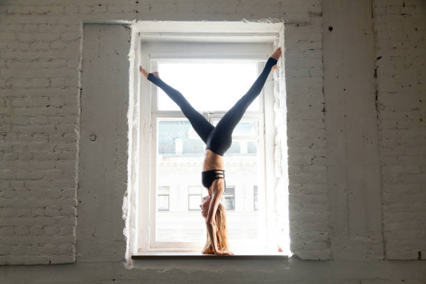 Young attractive woman in Downward facing Tree Pose, window sill stock photo