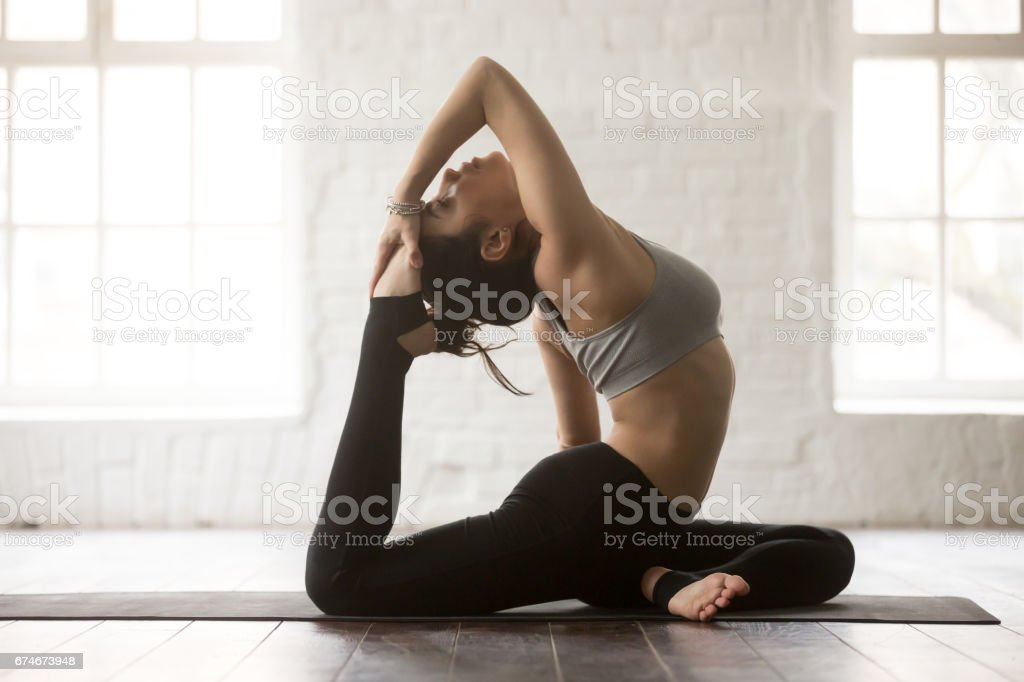 Young attractive woman in Eka Pada Rajakapotasana pose, white st stock photo