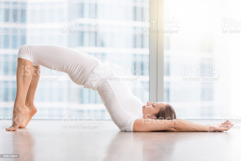 Young attractive woman in Glute Bridge pose against floor window stock photo