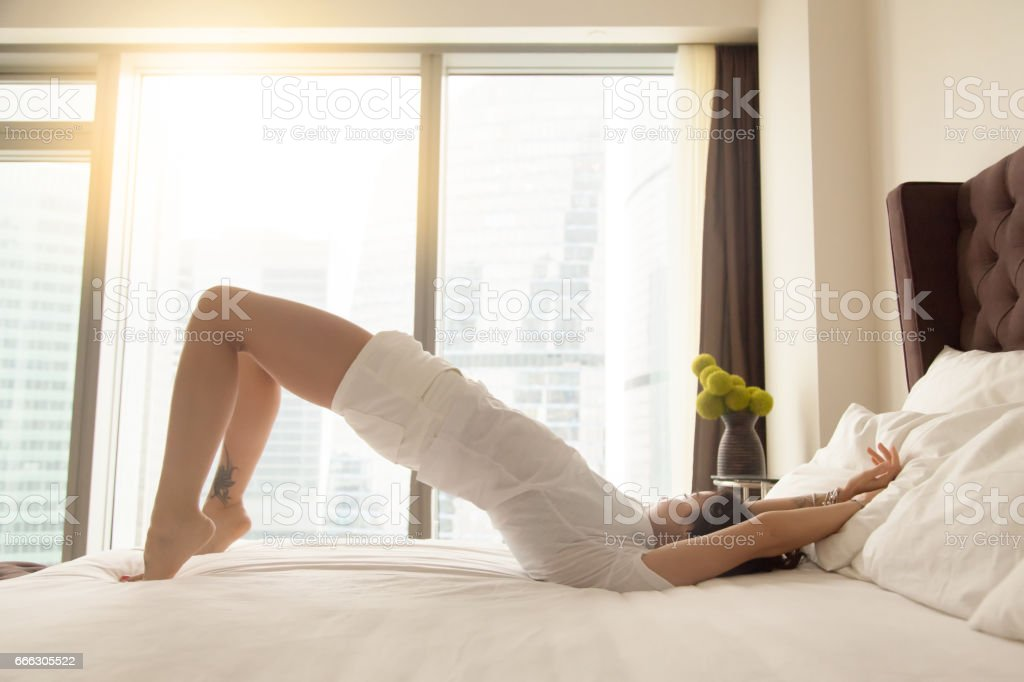 Young attractive woman in Glute Bridge pose on the bed stock photo