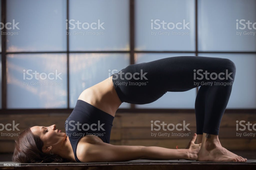 Young attractive woman in Glute Bridge pose, studio evening prac stock photo