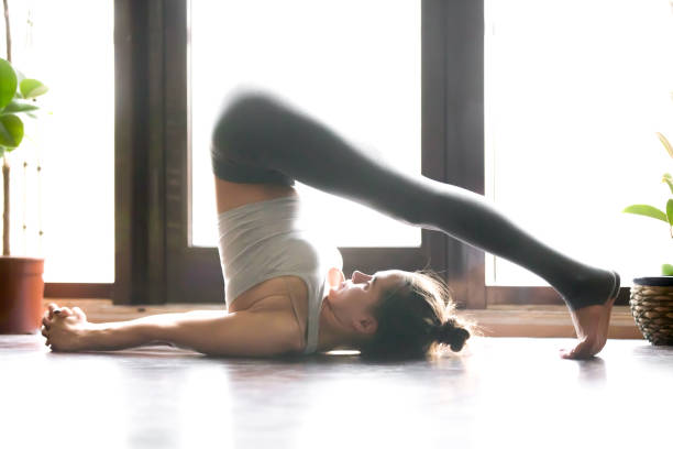 young attractive woman in halasana pose, home interior backgroun - yin yoga stock-fotos und bilder