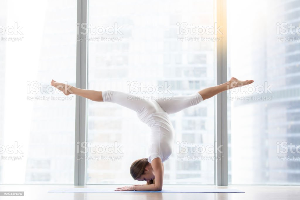 Young attractive woman in handstand, against floor window стоковое фото