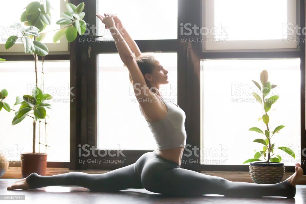 Young attractive woman in Hanumanasana pose, home interior backg stock photo