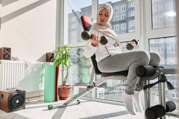 Young attractive woman in hijab, performs exercises with dumbbells, sitting on a bench at home gym. Young attractive woman in hijab, performs exercises with dumbbells, sitting on a bench at home gym. Bodybuilding, fitness, sport concept. exercise bench  stock pictures, royalty-free photos & images