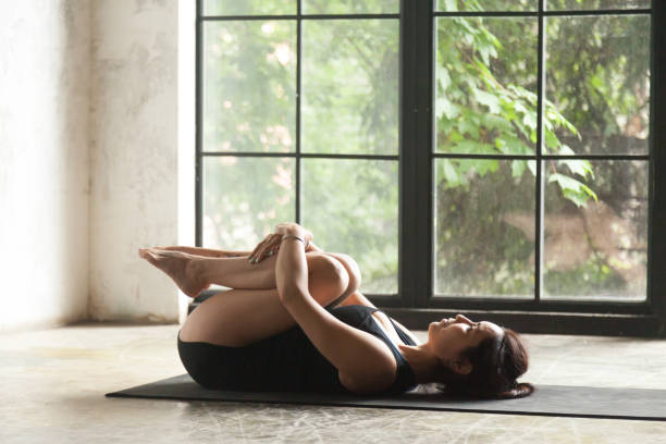 Young attractive woman in Knees to Chest pose, studio background Young attractive woman practicing yoga, lying in Knees to Chest exercise, Apanasana pose, working out, wearing sportswear, black shorts and top, indoor full length, studio background apanasana stock pictures, royalty-free photos & images