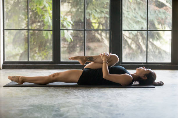 Young attractive woman in Knees to Chest pose, studio background Young attractive woman practicing yoga at home, stretching in Apanasana exercise, Knees to Chest pose, working out, wearing sportswear, black shorts and top, indoor full length, studio background apanasana stock pictures, royalty-free photos & images