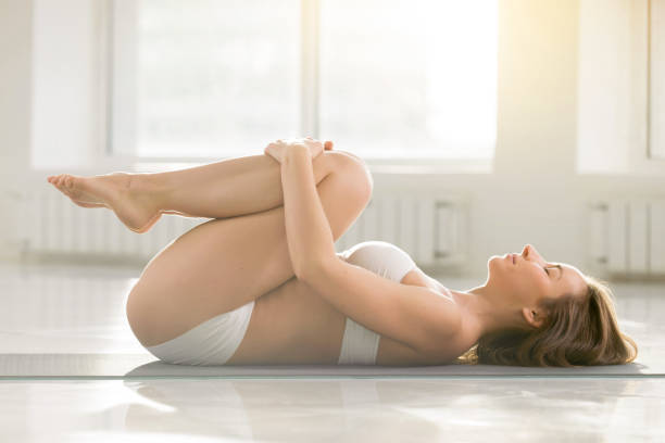 Young attractive woman in Knees to Chest pose, white background Young attractive yogi lady practicing yoga, doing Knees to Chest exercise, Apanasana pose, working out on floor, wearing sportswear, sport bra, shorts, indoor full length, white color room background apanasana stock pictures, royalty-free photos & images