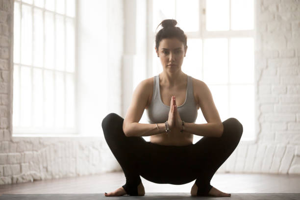Young attractive woman in Malasana pose, white loft studio backg Young attractive yogi woman practicing yoga concept, sitting in Malasana exercise, Garland pose, working out, wearing sportswear, full length, white loft studio background groyne stock pictures, royalty-free photos & images