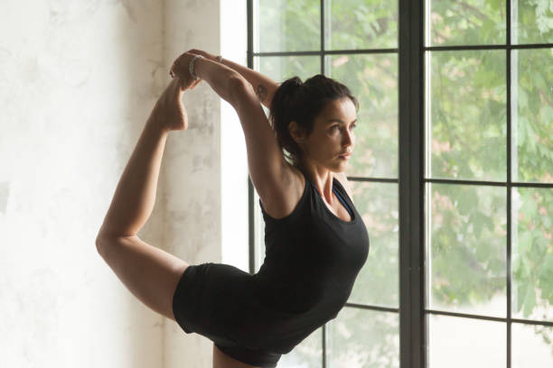 Young attractive woman in Natarajasana pose, closeup Young sporty woman practicing yoga at home, doing Natarajasana exercise, Lord of the Dance pose, working out, wearing sportswear, black shorts, top, indoor close up portrait image, window background whole-body gym system stock pictures, royalty-free photos & images