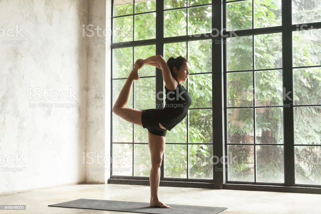 Young attractive woman in Natarajasana pose, studio background stock photo