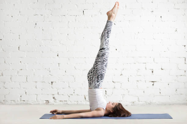 Young attractive woman in Niralamba Sarvangasana pose, white stu Young attractive woman practicing yoga, stretching in Niralamba Sarvangasana exercise, unsupported Shoulder stand pose, working out wearing sportswear, indoor full length, white studio loft background shoulder stand stock pictures, royalty-free photos & images