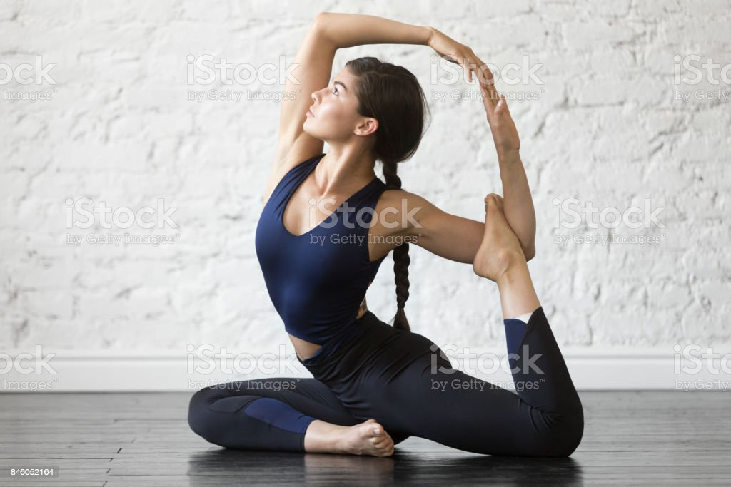 Young attractive woman in One Legged King Pigeon pose, studio Young woman practicing yoga, stretching in One Legged King Pigeon exercise, Eka Pada Rajakapotasana pose, working out, wearing sportswear, black top, pants, indoor full length, studio background 20-29 Years Stock Photo