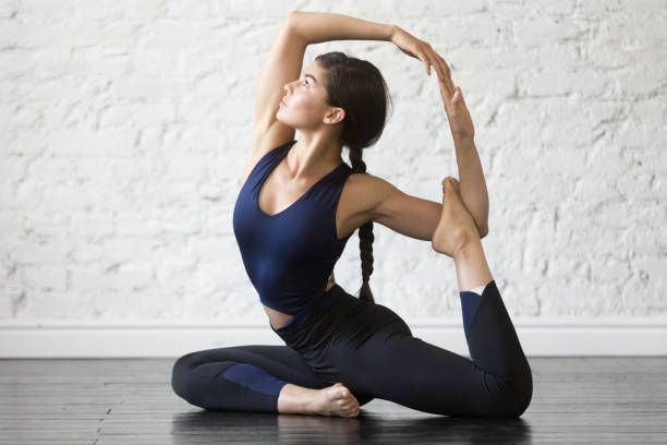 Young attractive woman in One Legged King Pigeon pose, studio Young woman practicing yoga, stretching in One Legged King Pigeon exercise, Eka Pada Rajakapotasana pose, working out, wearing sportswear, black top, pants, indoor full length, studio background bending over backwards stock pictures, royalty-free photos & images