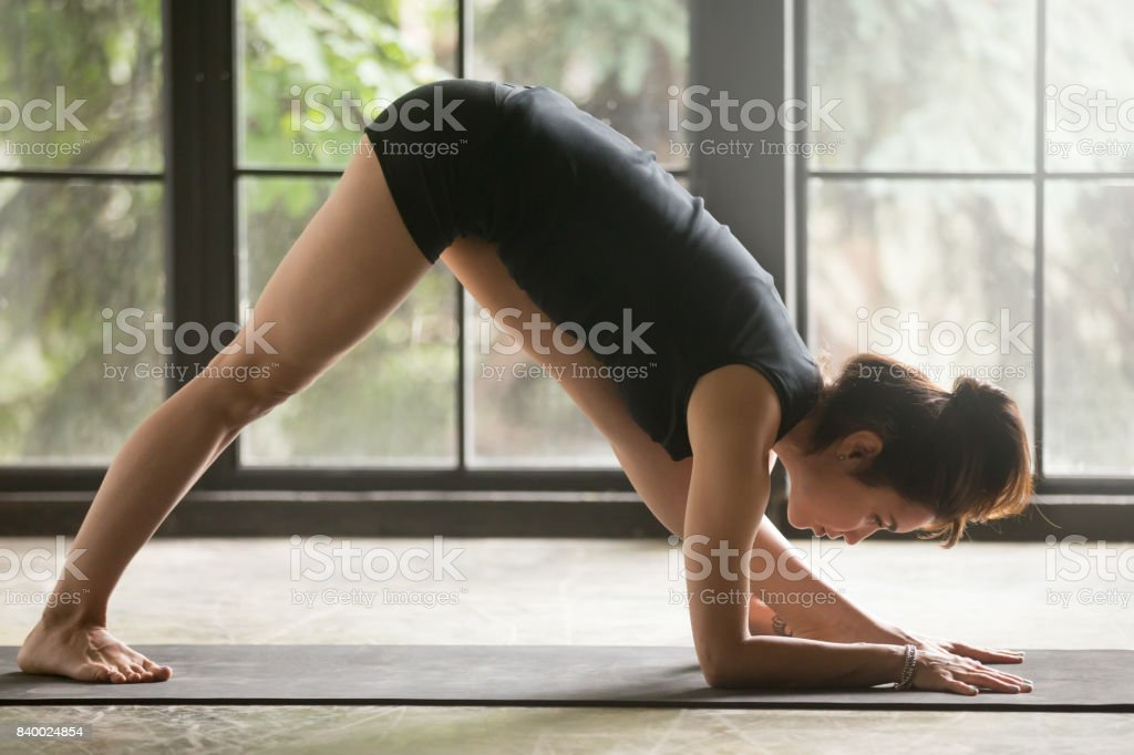 Young attractive woman in One Sided Fold pose, studio background stock photo