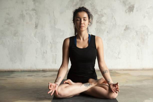 junge attraktive frau in padmasana darstellen, studio-wand-hintergrund - buddhist tattoos stock-fotos und bilder