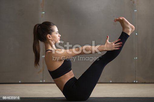 914755474 istock photo Young attractive woman in Paripurna Navasana pose, grey studio b 664635916